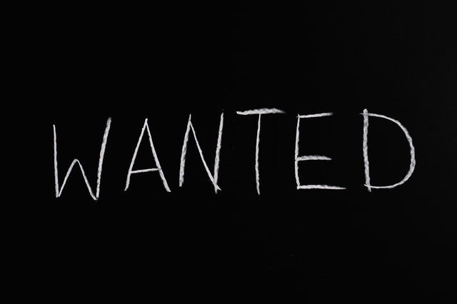 A black square with white writing that says 'wanted'