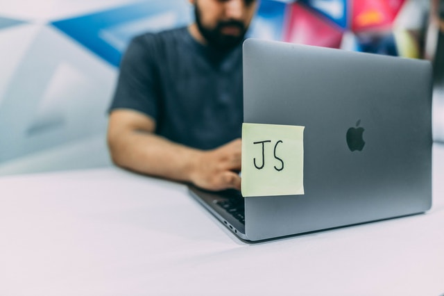 A JavaScript Developer working on a JavaScript project at a Macbook Pro