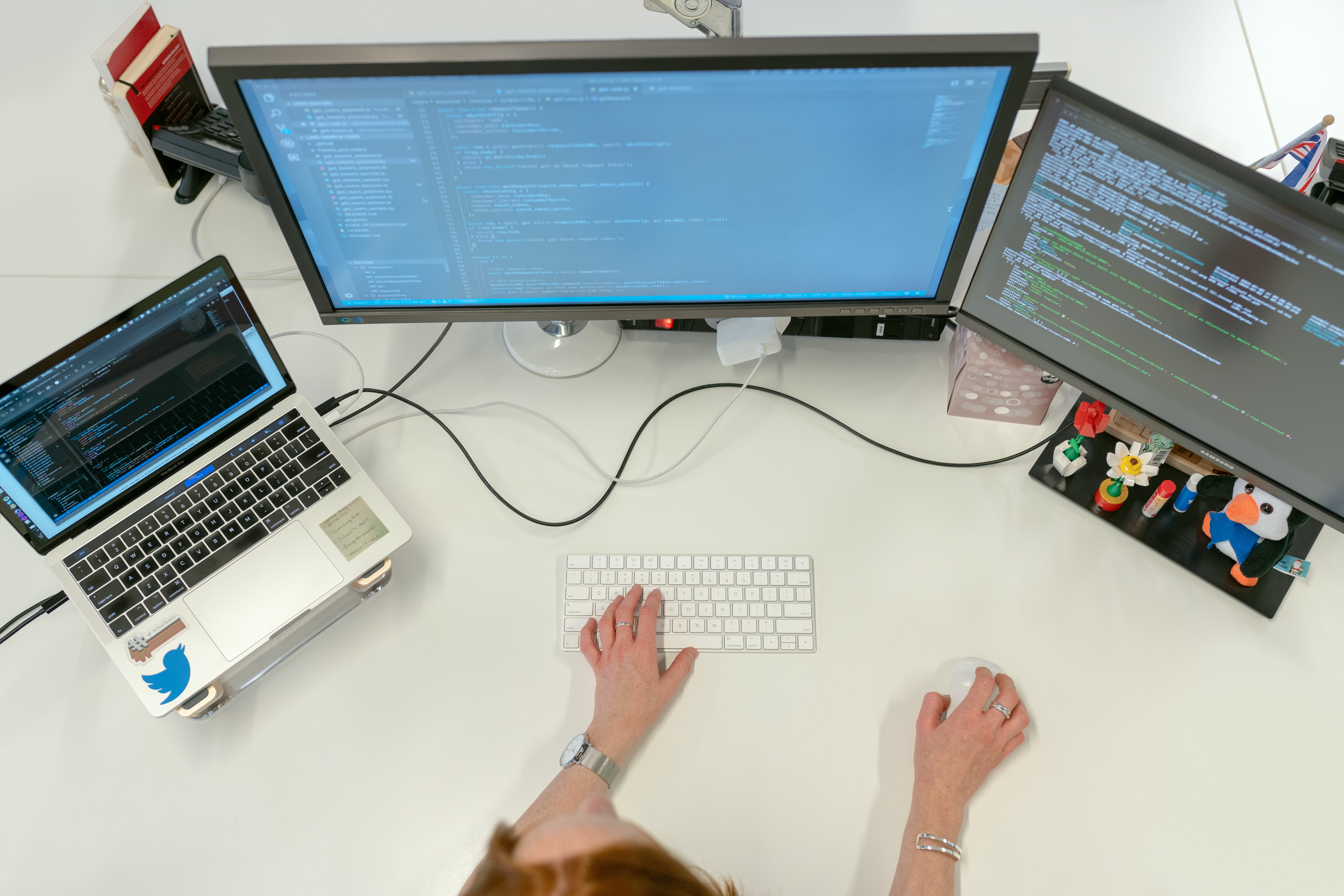 Image of a trio of computer screens with someone working at them.